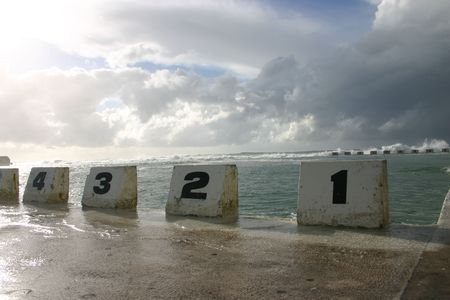 Numbered starting blocks at Merewether ocean baths, Newcastle Australia. Storm clouds and stormy surf in background.