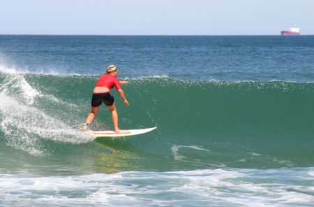 A woman surfer competes in professional surfing competition at Newcastle beach Australia Stock Photo