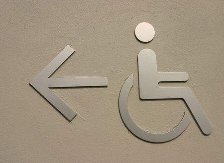A sign mounted on the wall directing disabled access photo