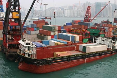 A barge being loaded with containers at a container terminal in Victoria Harbour - Hong Kong