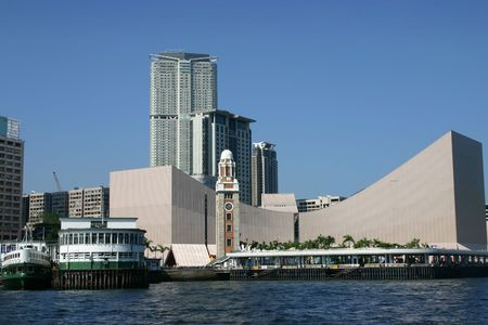 Tsim Sha Tsui from Victoria Harbour - Hong Kong. Iconic clocktower - ferry terminal and Hong Kong cultural centre