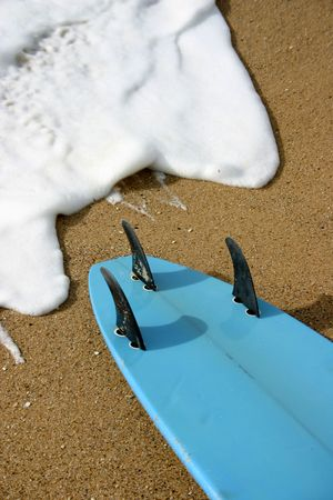 surfboard fin: A blue surfboard sitting on the sand about to be hit by a white foamy wave