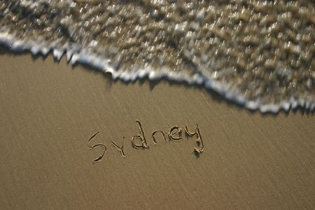 deliberate: Sydney written in the sand at the beach. Deliberate motion blur of wave  Stock Photo