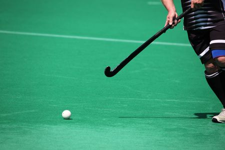 A field hockey player about to pass the ball