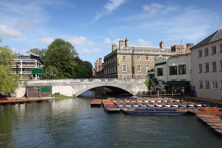 View of the river Cam in Cambridge complete with iconic punts tied at the side of the river waiting to hired.