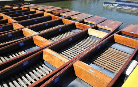 punting: A group of wooden punts tied together on the river Cam in Cambridge - England. Punting is one of the university cities iconic activities.