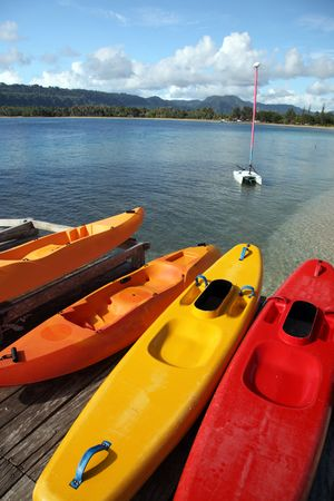 Tropical holiday scene in Vanuatu in the South Pacific. Colourful sea kayaks and sailing boat in the background. photo