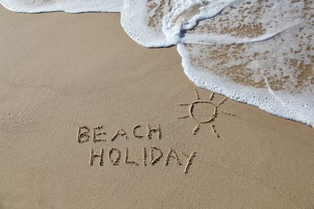 Beach Holiday written in the sand with a sun symbol and wave Stock Photo - 7293959