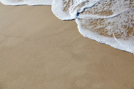 A wave rolls up the sand at the beach. Plenty of room to add your own text or design Stock Photo - 7306357