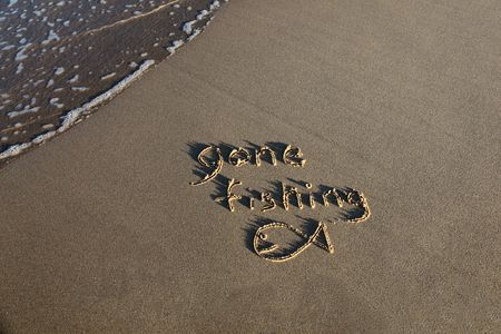 Gone fishing written in the sand at the beach with a small wave lapping at the edge of the scene. Stock Photo