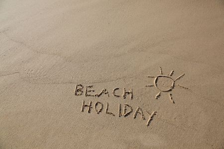 Beach Holiday written in the sand with a sun symbol. Stock Photo - 7474338