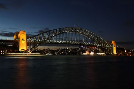 A night view of one of Sydneys most famous landmarks. The Sydney Harbour Bridge. The bridge was opened in 1932 and is well known by its nick name of the coathanger Ferry light blur mid-frame.
