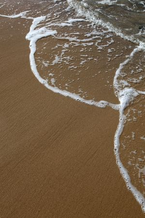 A wave rolls up the sand at the beach. Room to add your own text. Stock Photo - 7677837