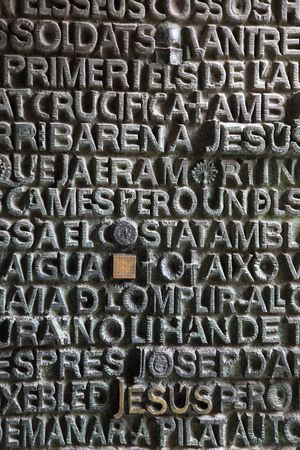 Closeup detail of one of the doors at the famous Sagrada  church in Barcelona. The church was designed by the famous architect Antoni Gaudi and is still under construction which started in 1882. This door features passages from the bible in various langua
