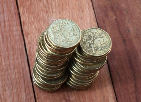 Two piles of Australian one dollar coins on a wooden background. Shallow depth of field focus. photo