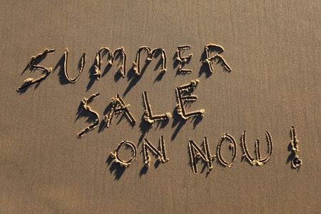 Summer Sale On Now written in the sand at the beach.