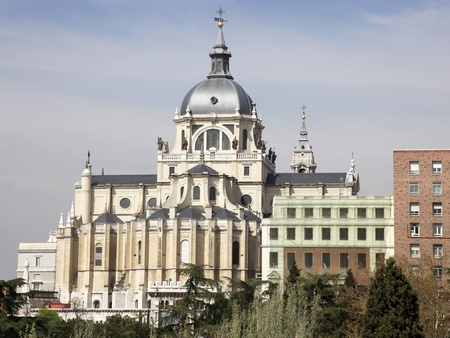 adjacent: Santa Maria la Real de La Almudena is a Catholic cathedral in Madrid adjacent to the Royal Palace.