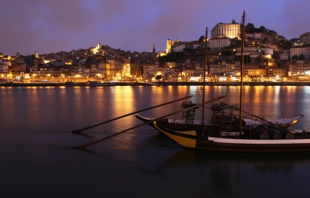 oporto: View of the Ribeira area - Porto across the Douro River at night. Note slight motion blurr on the tradition port carrying Rabelo boats.