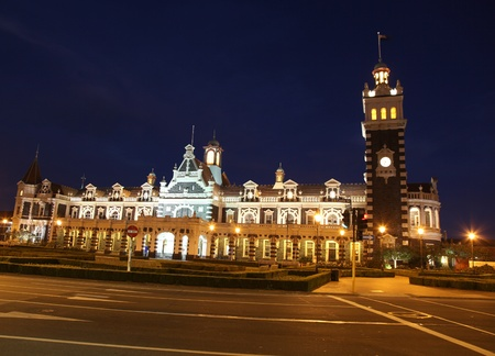 nightime: Dunedins famous historic railway station at nightime. - Dunedin New Zealand. This ornate Flemish Renaissance-style building was opened in 1906 and is a famous landmark in the University city.