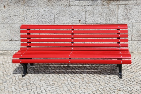 painted wood: A bright red park bench with stone wall background.