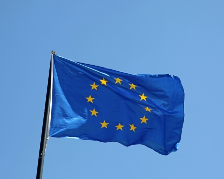 An European Union flag flying in the wind with blue sky background photo