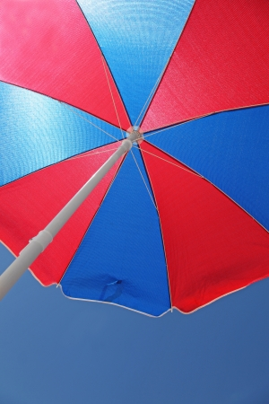 underneath: A blue and red beach umbrella from underneath. The symbol of summer.