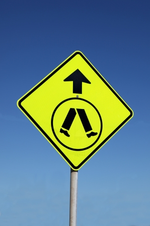 traffic rules: A bright yellow pedestrian crossing sign on blue sky background.