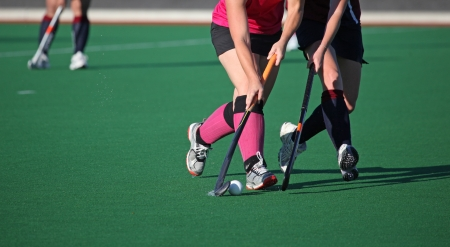 Two women players contest for the ball in a game of field hockey