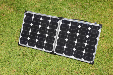 Portable solar panels on green grass  Solar power has become a mainstain of the  glamping  camping recreation