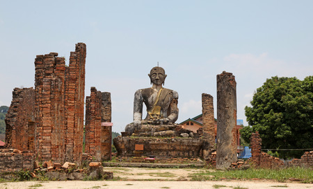 bombings: The ruin of Wat Phia Wat near Phonsavan in Laos. The area was subject to bombing during the Vietnam War and this buddha statue and some walls are all that remain of this temple. The local people have decided to leave the temple in a ruined state as a remi