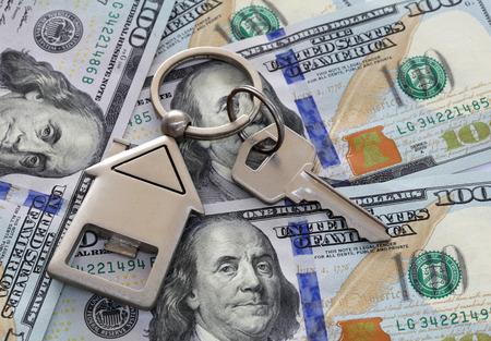 investment real state: Notas de cien dólares americanos con llave de la casa y llavero. Tiro anguloso hay notas completas se muestran.
