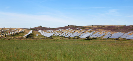 room for copy: A large solar power station located in a green field with blue sky background. Room for copy. Stock Photo