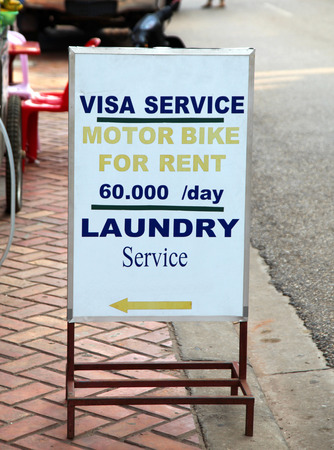 motobike: A typical sign in South East Asia advertising the essential travel services to backpackers including travel Visas , motobike rental and laundry. This sign was located in Vientiene Laos Stock Photo