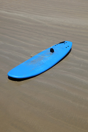 learners: A soft blue malibu surfboard on the sand at the beach. Board such as these a perfect for learners to use and are commonly used in surf schools. Stock Photo