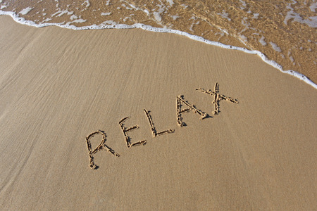 rolling up: Relax written in the sand at the beach with wave rolling up Stock Photo