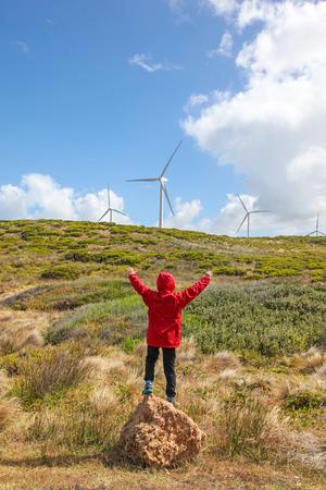 turbina: Un niño de pie en frente del paisaje costero con turbinas de viento en el fondo en la costa sur de Victoria - Australia. Foto de archivo