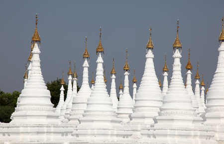 White stupas at Kuthodaw Pagoda in Mandalay Myanamar (Burma). This temple complex began construction in 1860 when the capital city was relocated to Mandalay. Stock Photo