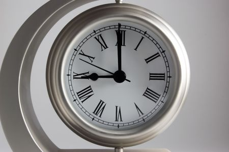 Metal clock with white face showing nine oclock