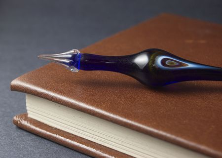 Antique blue glass pen on leather bound book