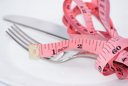 tape-measure and fork white background isolated Stock Photo