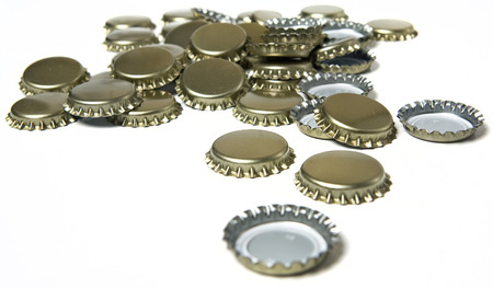 A variety of bottle caps lay on a white background