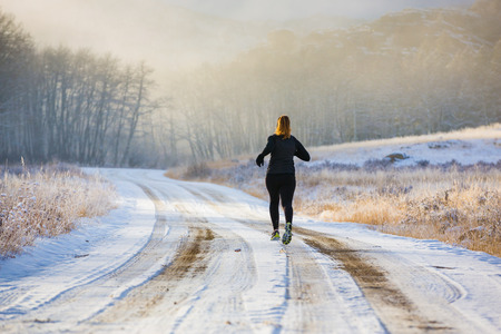 outdoor exercise: A female trail runs in the fog and snow of winter.