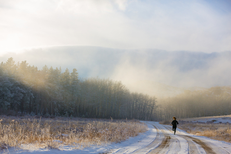 winter: A female trail runs in the fog and snow of winter.