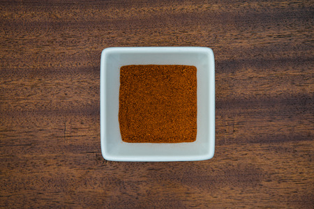 Paprika sits in a square white bowl on a real wood background. Imagens