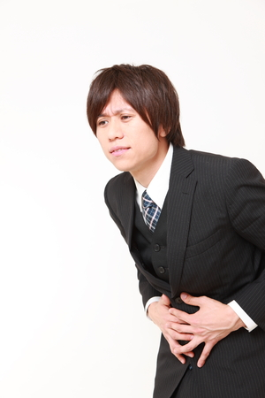 young Japanese businessman suffers from stomachache