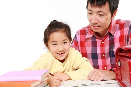father helping his daugther doing homework photo