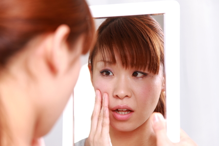 young Japanese woman worries about dry rough skin Stock Photo