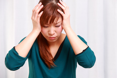 young Japanese woman suffers from head ache photo