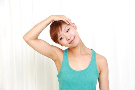 自己の首のストレッチを行う若い女性