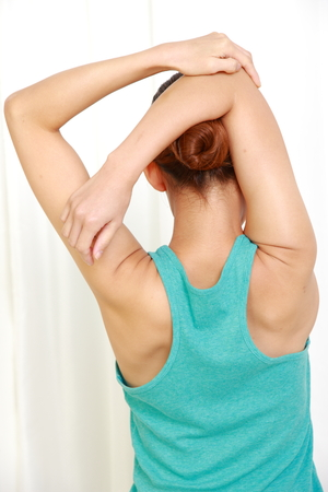 young woman doing self shoulder stretch Stock Photo